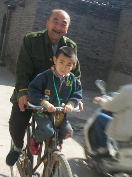 Abuelo y nieto compartiendo bicicleta