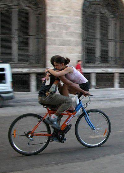 Pareja de enamorados compartiendo bicicleta