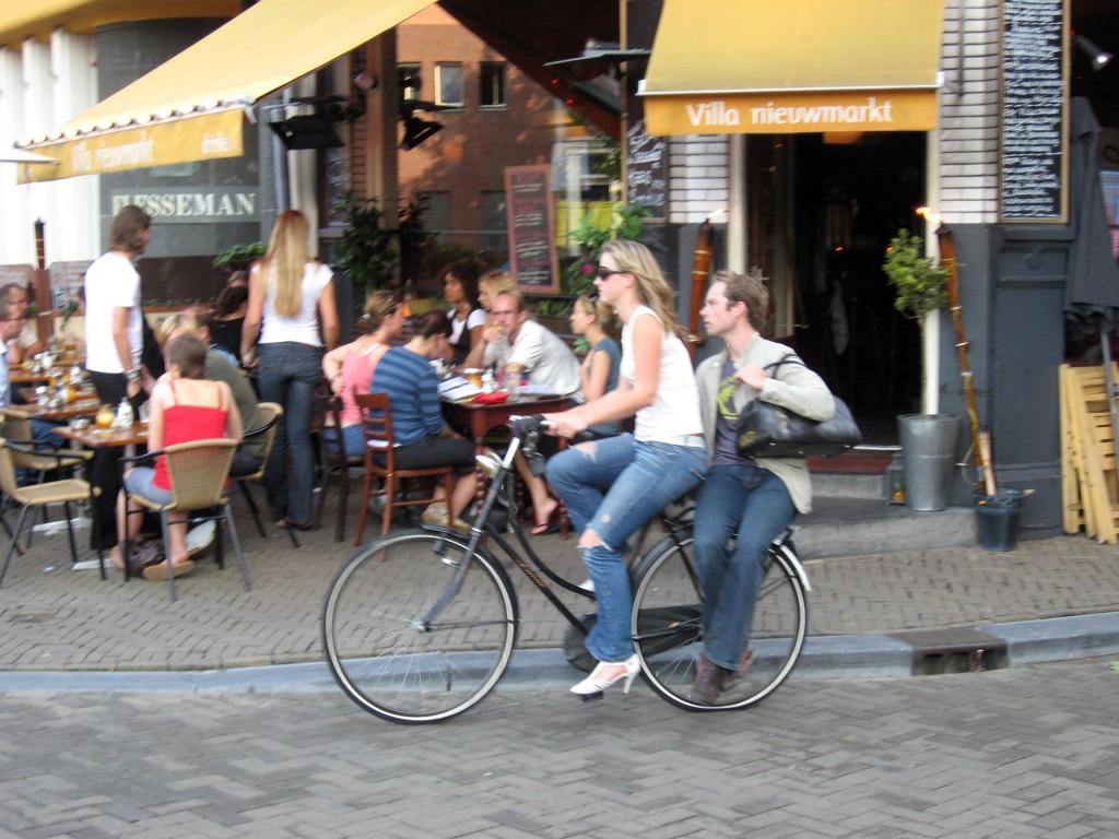 Chica y chico compartiendo bicicleta en Amsterdam