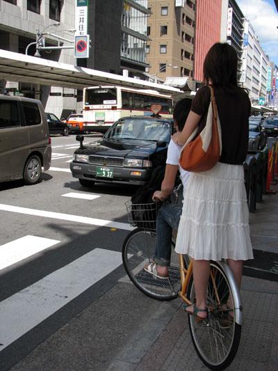 De pie sobre la rueda trasera de la bicicleta en Tokyo